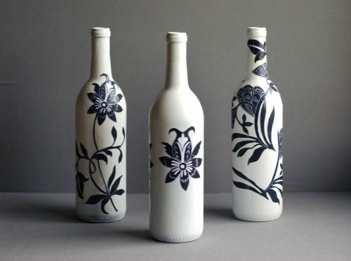 drei weiße flaschen mit servietten mit schwarzen blumen