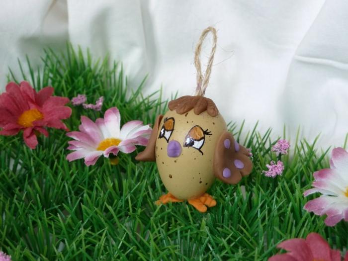 eine Huhn in brauner Farbe, künstlicher Gras und künstliche Blumen - so bildschön