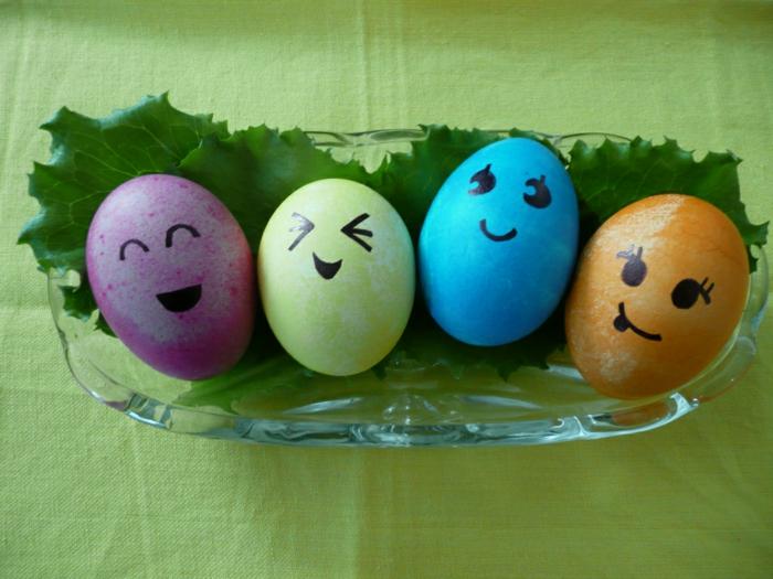 Ostereier Gesichter in vier verschiedenen Farbe in einer Schale mit Blätter