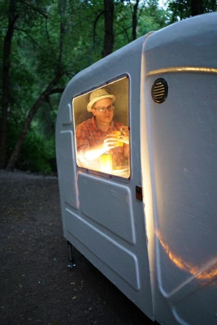 hier ist ein mann mit hut brillen in einem weißen gemütlichen fahrrad wohnwagen im wald