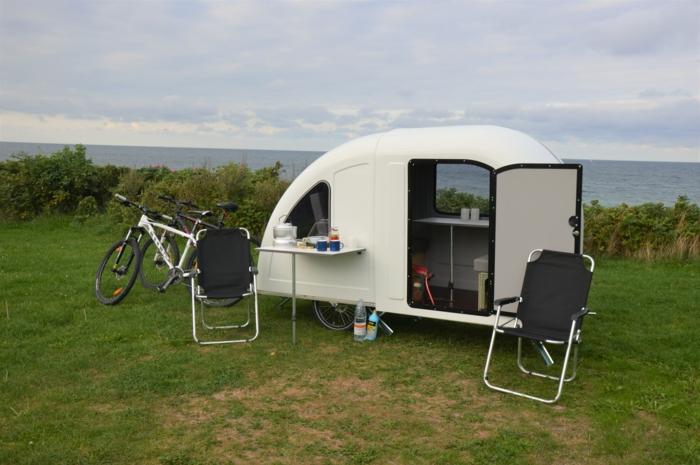 ein weißes kleines wohnmobil mit tisch, zwei fahrräder und zwei stühle
