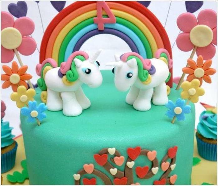 eine grüne einhorn torte mit blumen, regenbogen und zwei weißen einhörnern