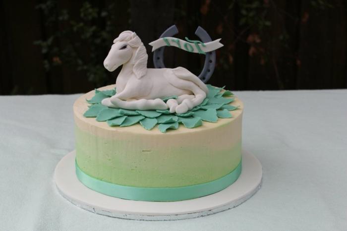 eine grüne torte mit einem weißen einhorn - idee für einhorn kuchen