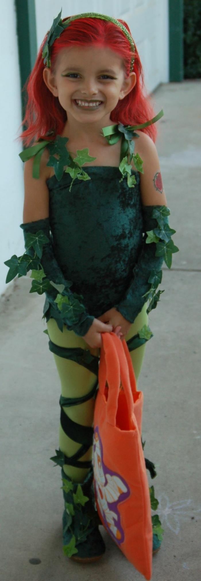 niedliches Mädchen mit grüner Strumpfhose und grüne künstliche Blätter