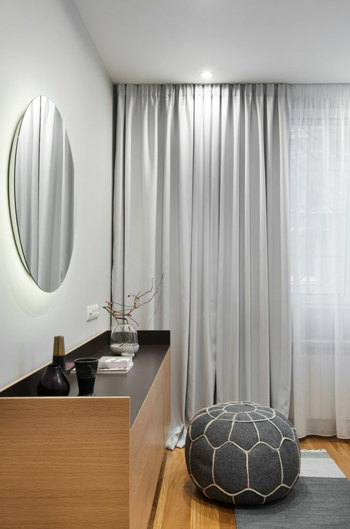 moderne vorhänge in silbern, schrank aus holz, runder spiegel
