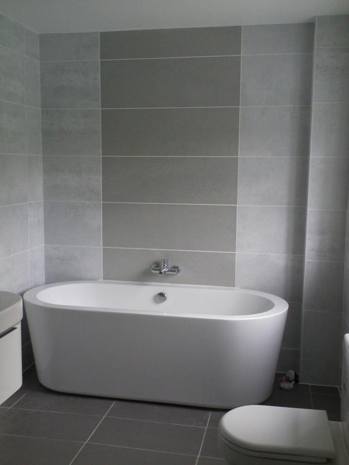 geometrische Form von Kacheln über die Badewanne, schwarze Bodenfliesen