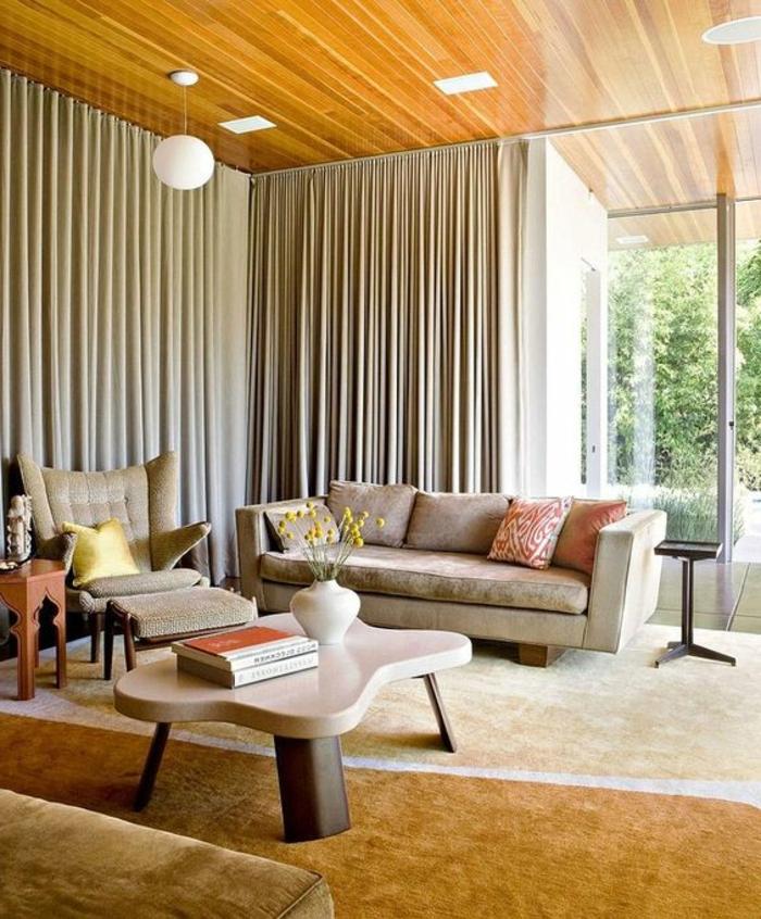 wohnzimmer in naturfarben mit großem fenster mit beigen gardinen