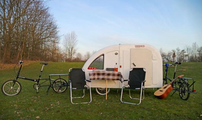 hier ist ein fahrrad wohnwagen, tisch, stühle und zwei schwarze stühle
