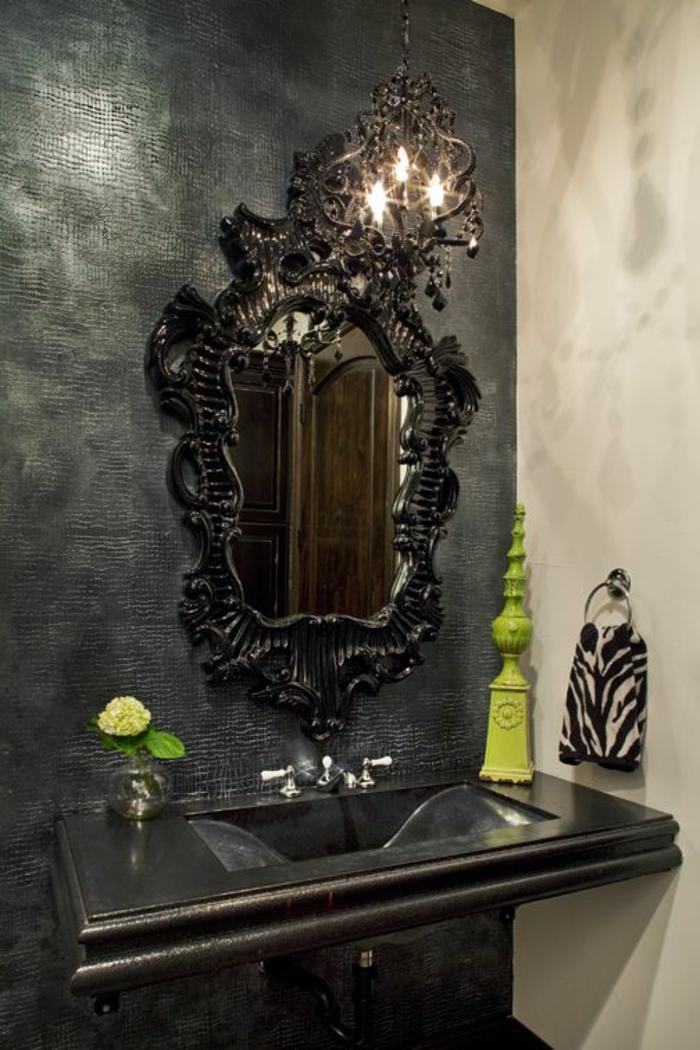 Badezimmer mit einer schwarzen Wand und einer weißen Wand, Gothic-Spiegel und schwarzem Waschbecken