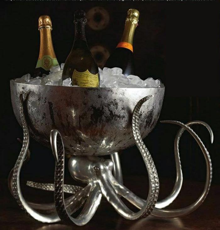 ein Eisbehälter aus Metall in der Form einer Oktopode mit drei Champagne-Flaschen und vielen Eiswürfeln
