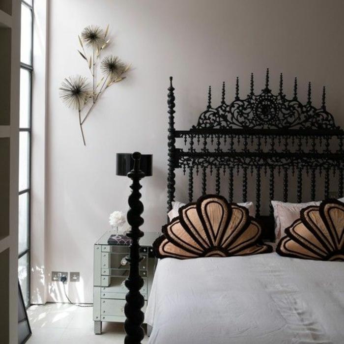 gotisch eingerichtetes Schlafzimmer mit Doppelbett aus Metall mit vielen Ornamenten, Musterkissen, Wanddeko
