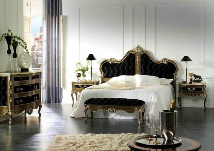 großes Schlafzimmer mit Doppelbett im gotischen Stil, Gothic-Kommode in Schwarz und Gold, cremeweißer Teppich