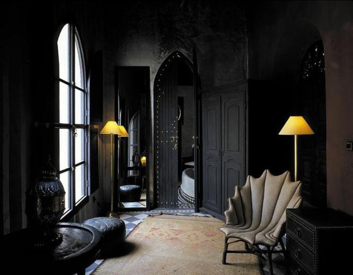 Relaxecke mit Gothic-Sessel, Teppich in Naturfarben, schwarze Wände, schwarze Kommode, zwei Stehlampen