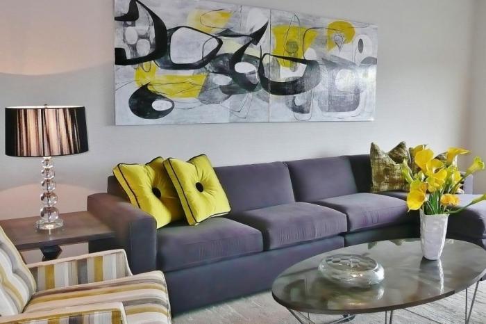 wohnaccessoires, großes graues sofa mit zwei gelben deko kissen, gelbe blumen auf dem tisch