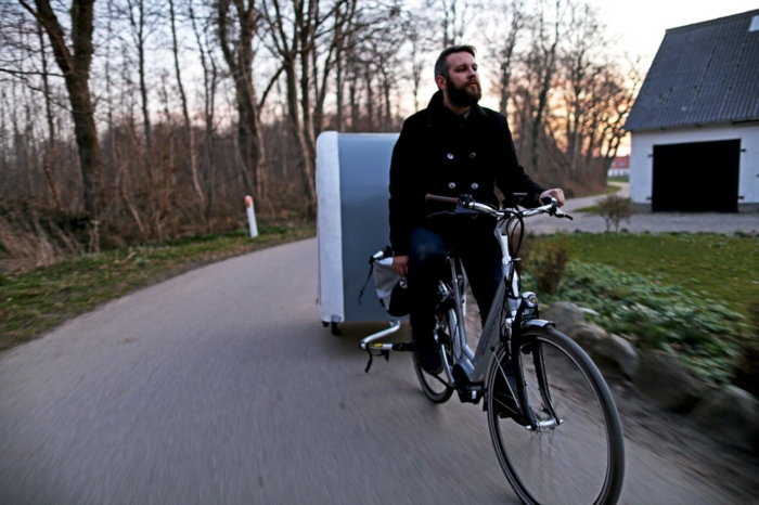 ein radfahrer mit einem schwarzen mantel und ein fahrrad mit einem fahrrad wohnwagen