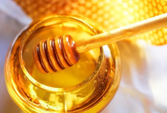 Glas mit goldenen Honig und ein hölzerner Honiglöffel