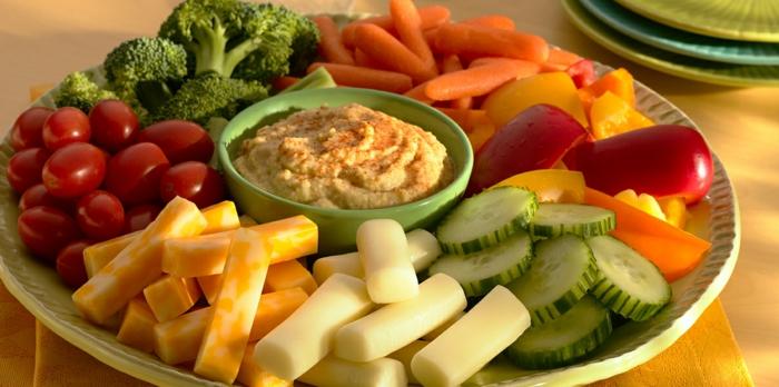 kichererbsen zubereiten in form von hummus mit gemüse und käse servieren und genießen