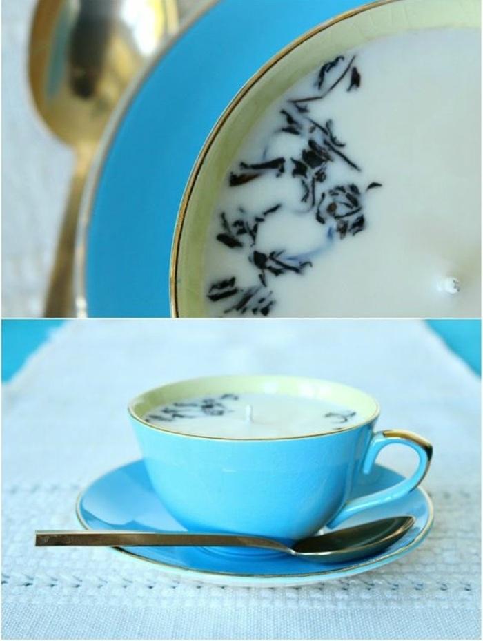 blaue teetasse mit weißer kerze mit schwarzen elementen