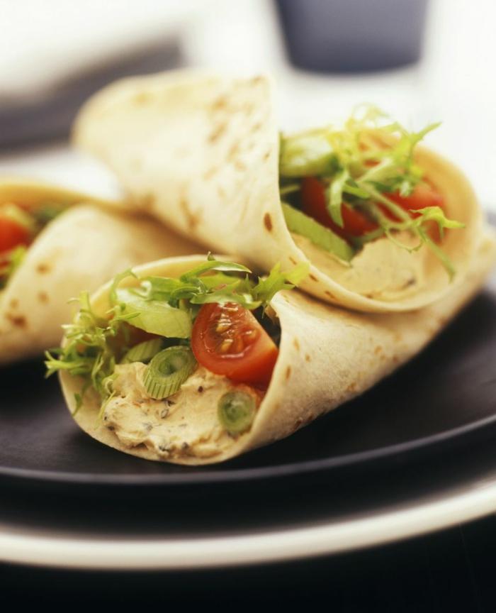 tortillas voll mit hummus tomaten grüner kopfsalat knoblauch und zwiebel und andere gemüse
