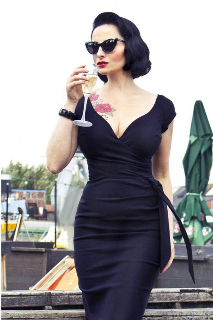 kleid in schwarz, mit dekolletee, sonnenbrillen, armband, tattoo