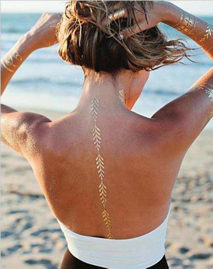 tattoo ideen dezente linie in goldener farbe auf dem rücken frau mit blonden haaren am strand