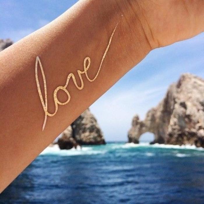 tattoo vorlagen frauen liebe mit goldenem stift schreiben tattoo am arm meer harmonie romantik