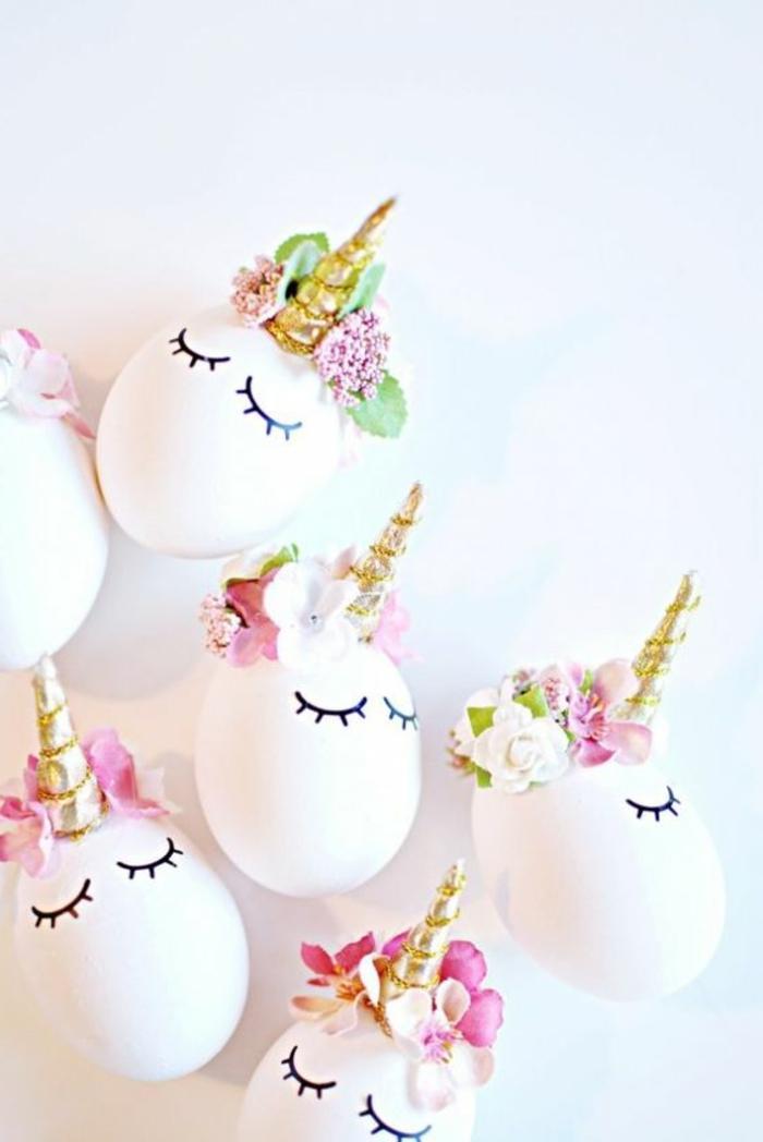 weiße Eier lustig wie Einhörner mit goldenen Hörner und Blumen zur Dekoration