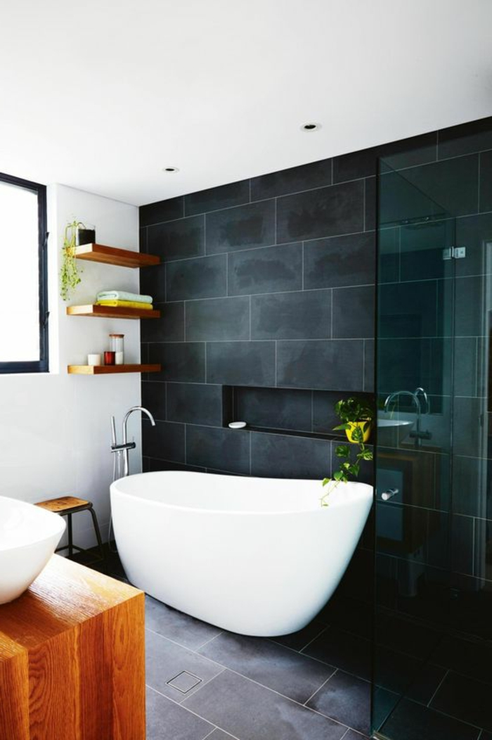 minimalistisch eingerichtetes Badezimmer mit schwarzen Fliesen, weißer Badewanne und Holzschrank, Duschkabine