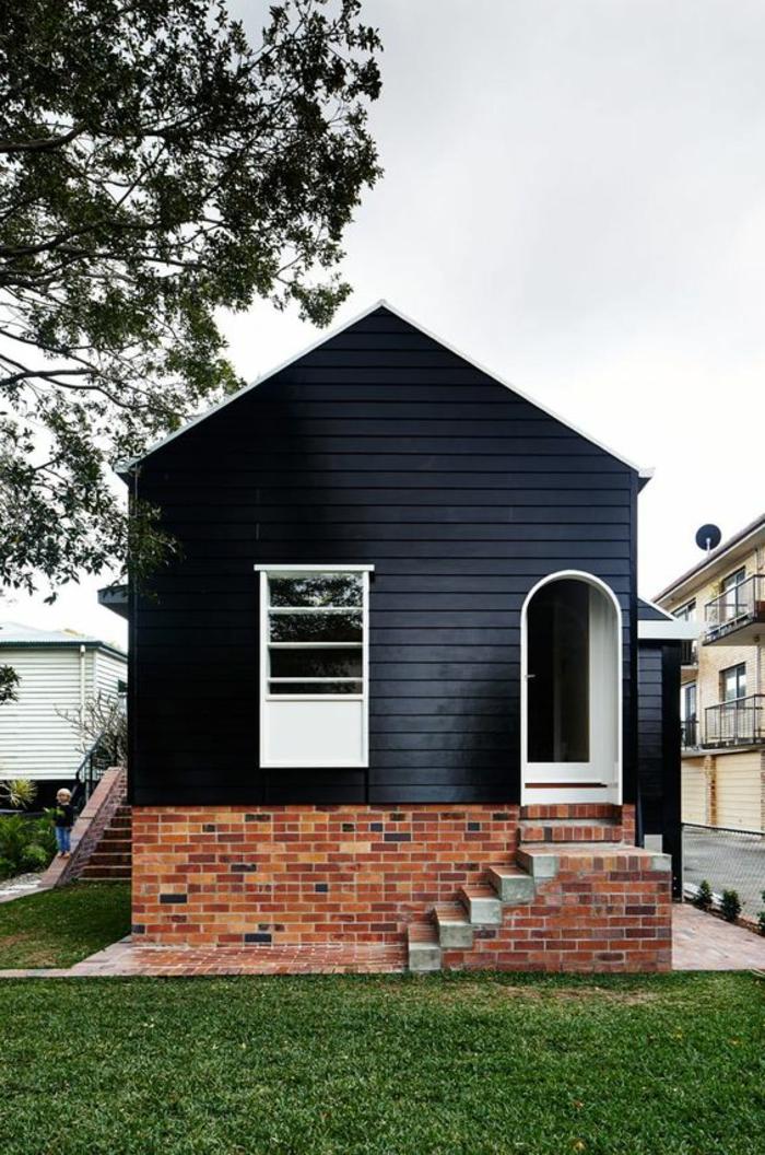 ein kleines Holzhaus im minimalistischen Stil, gestrichen in Schwarz, Ziegelbau, Treppen, minimalistische Architektur