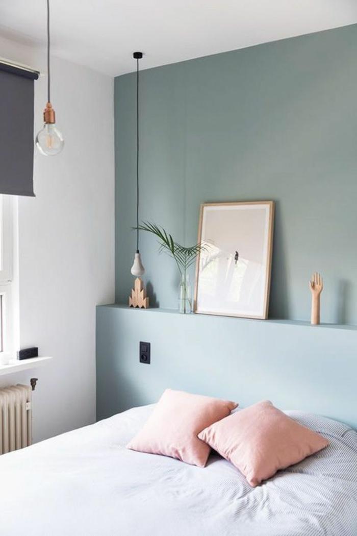 Minimalismus im Schlafzimmer: blaue Wand, Wandregal, Dekos, hellpinke Kissen, weiße Bettwäsche