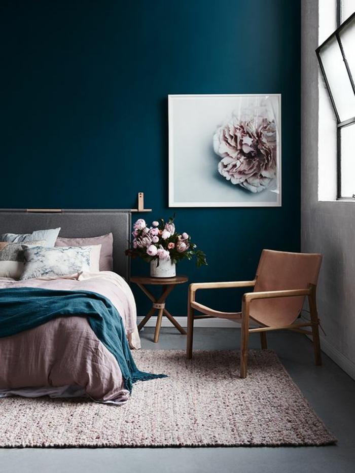 Schlafzimmer mit blauügrüner Wand, Doppelbett, Musterkissen, runder Holztisch mit Blumen, Lederstuhl