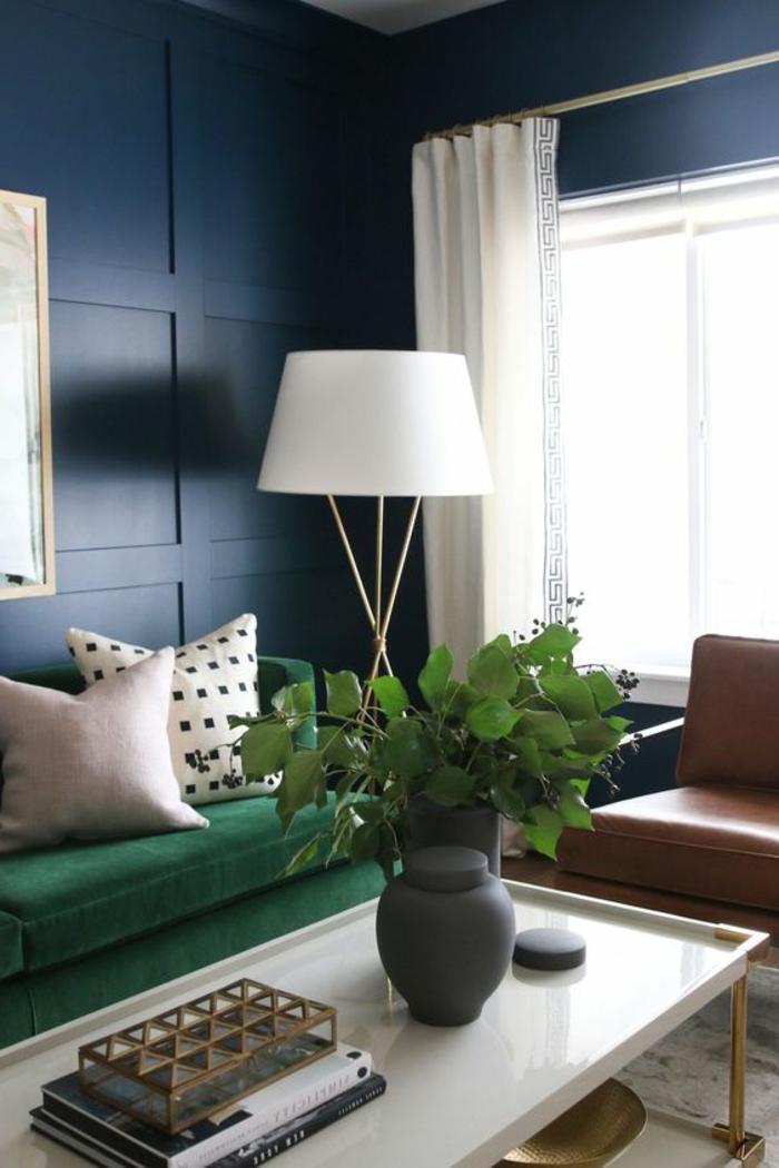 Wandverkleidung aus Holz, gestrichen in Blau, Stehlampe, grüne Polstercouch, Pflanzen, Ledersessel