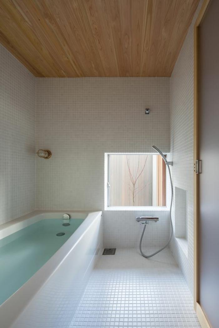 Badezimmer mit eingebauter Badewanne, weißen Fließen, viereckigem Fenster neben der Dusche, Holzdecke