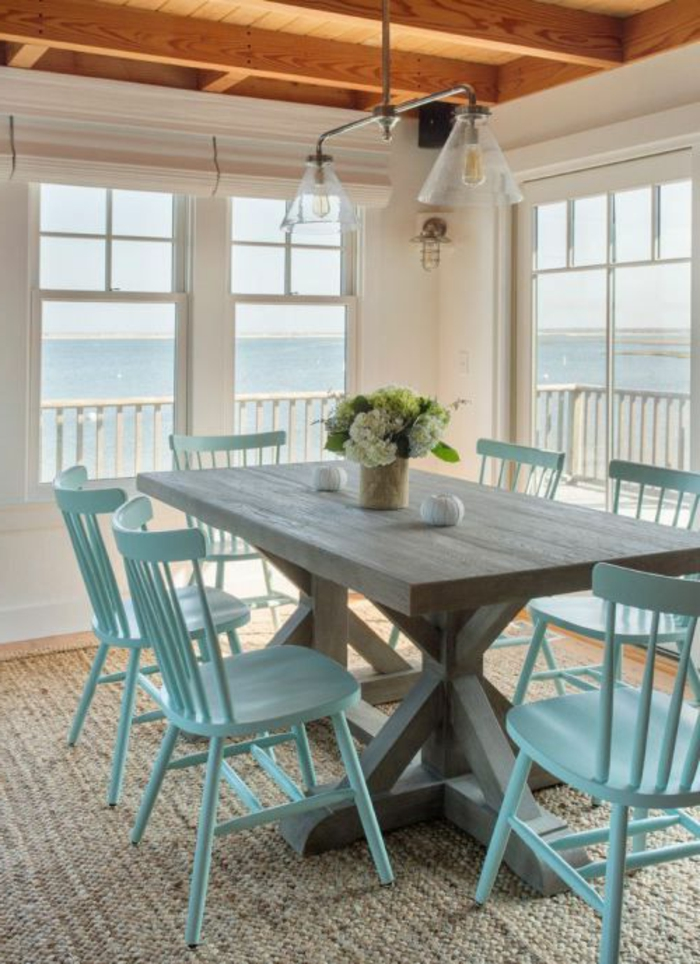 minimalistisches Esszimmer mit Meeresaussicht, Esstisch aus massivem Holz, blaue Holzstühle, Tischdeko