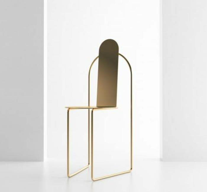 ein Stuhl aus Metall in Goldfarbe mit minimalistischem Design, ohne Armlehnen, mit zwei Beinen