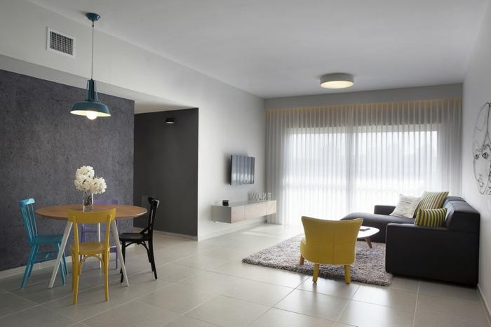 Wohnzimmer mit hellen Bodenfliesen, runder Esstisch aus Holz, 3-Stuhl-Set, schwarze Eckcouch, Fernseher