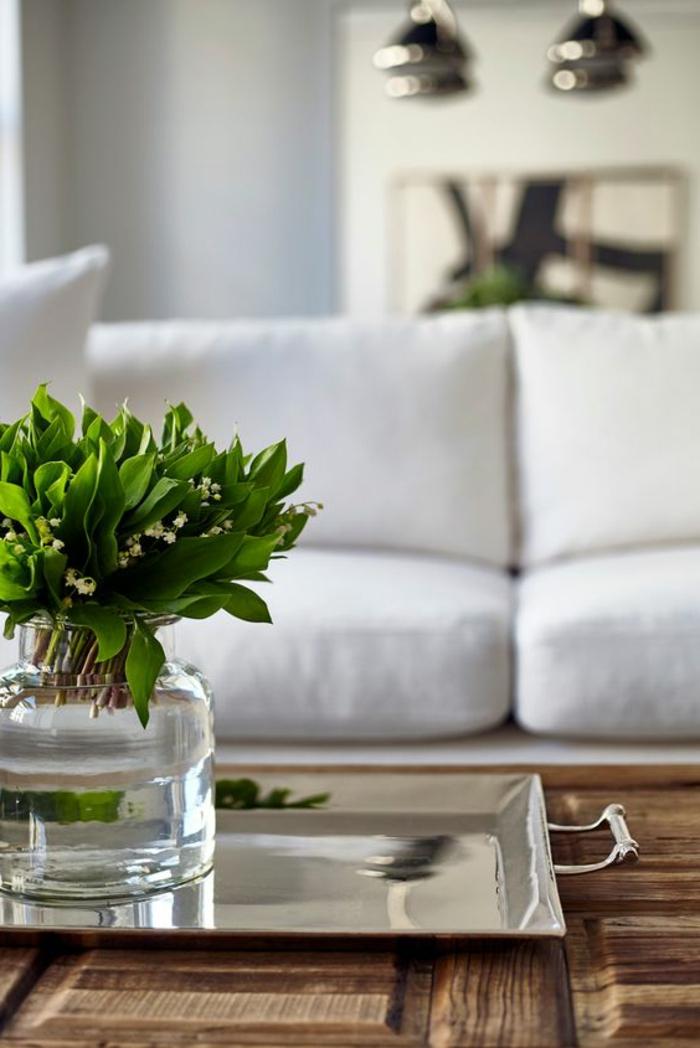 Couchtisch aus massivem Holz mit Pflanzendeko auf einem Metalltablett, weiße Couch