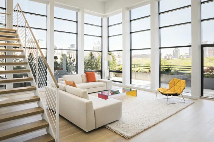 zweistöckiges Haus mit Fenstern bis zum Boden, weißen Couchen mit orangen Kissen, Glastisch und gelbem Relax-Stuhl