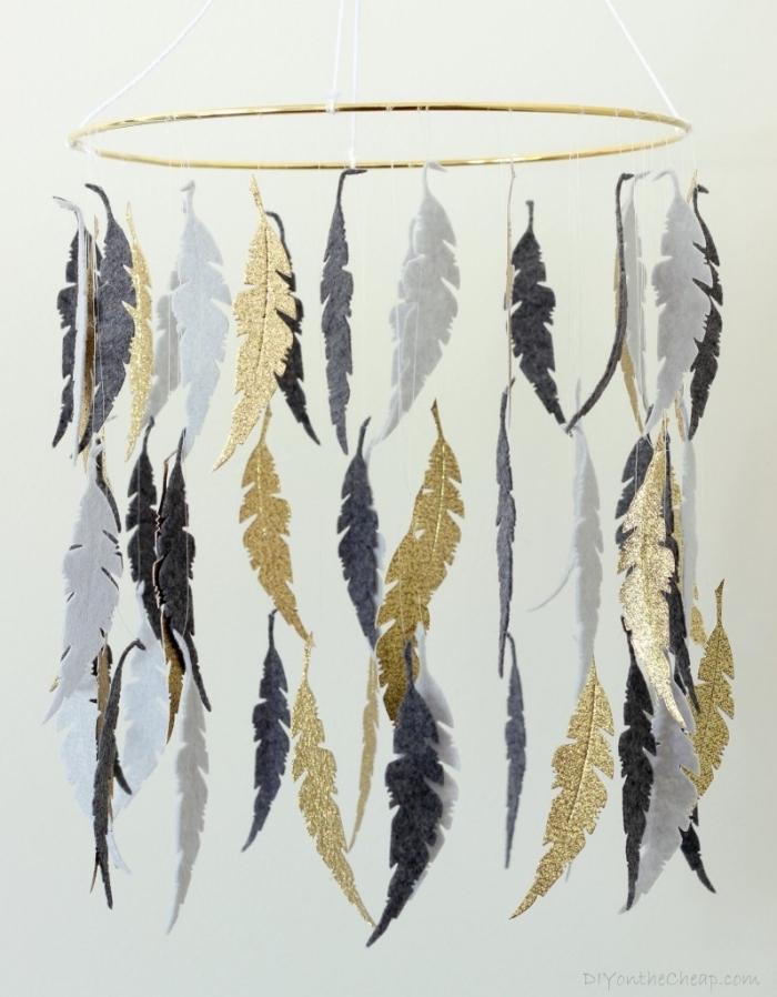 mobile selbst basteln, goldener metallener ring, blaue, goldene und silberne feder aus stoff