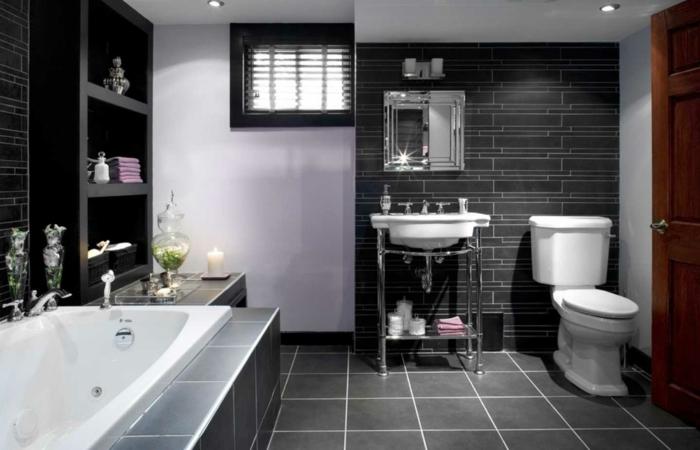 schwarze Fliesen in verschiedener Forme und Größe, neben der Badewanne