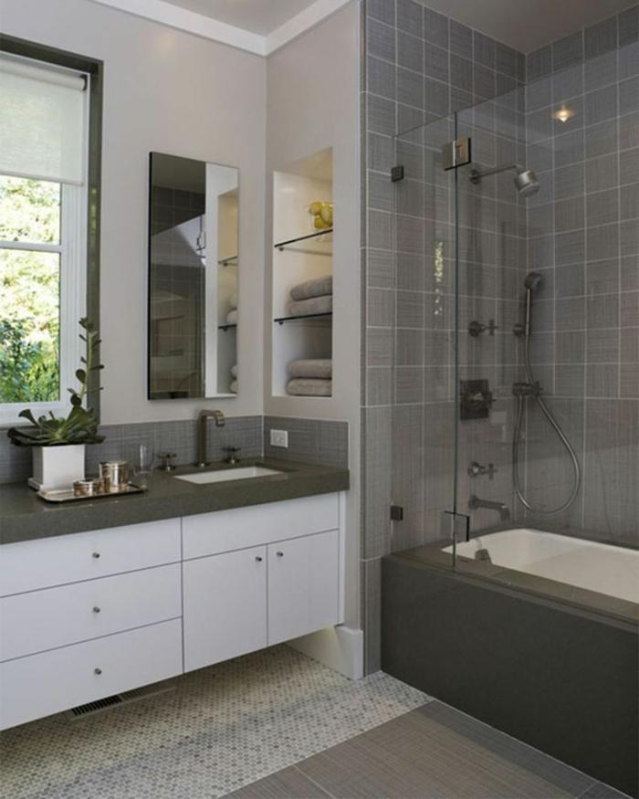 graue Wände von Duschkabine, Mosaikfliesen an dem Boden, Fenster mit Rollos