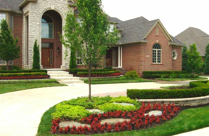 rote Blumen und gelbe Blumen um einem Baum, großes Haus Vorgartengestaltung