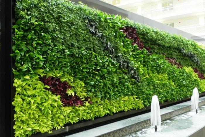 grüne Wand mit einem Springbrunnen davor - vertikaler Garten