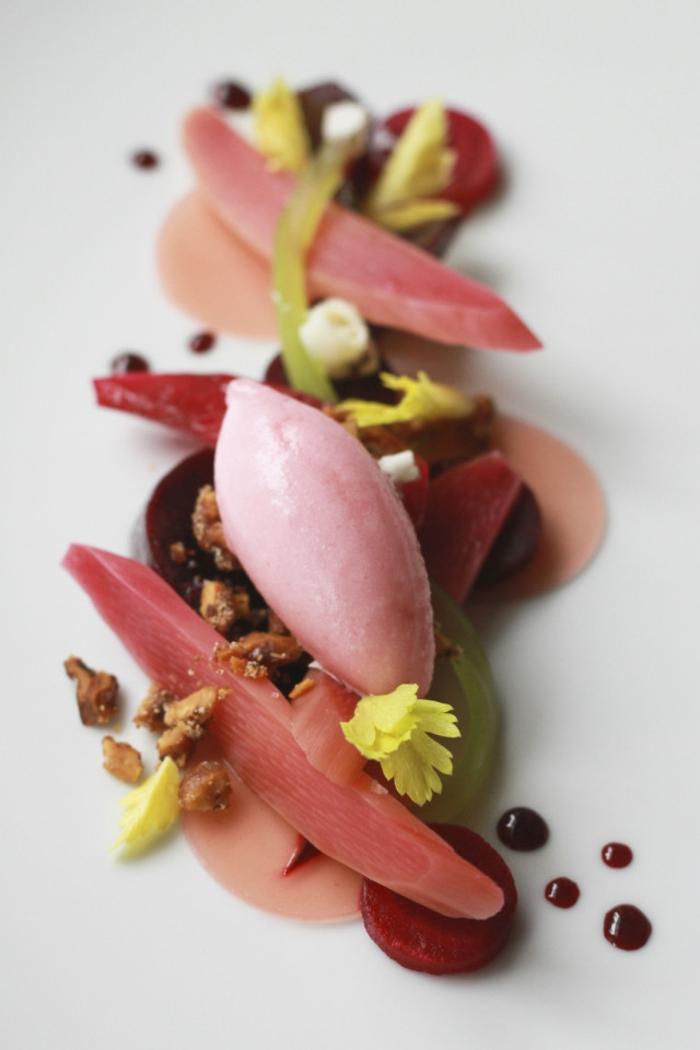 Dessert mit Rhabarber, Eis aus Rhabarber, Nüsse, Rhabarbersoße, essbare gelbe Blumen