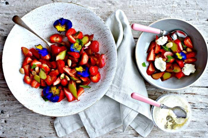 Rhabarbersalat mit Erdbeeren, Veilchen und Mascarpone Creme in eleganten Schüsseln aus Porzellan