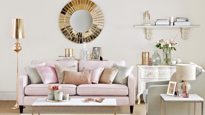 zimmer deko mit einem großen spiegel in der mitte von der wand, goldenes spiegel, rosa sofa, kleiner kaffeetisch
