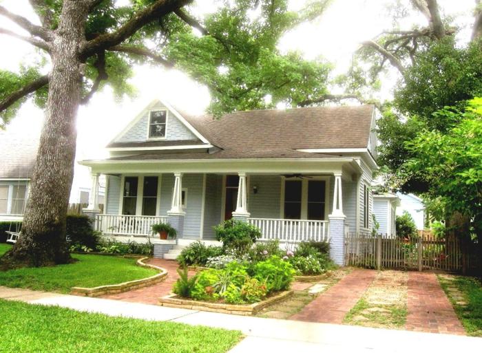 kleines Haus mit schönen Vorgarten, kleine Zierstrauche und Blumen
