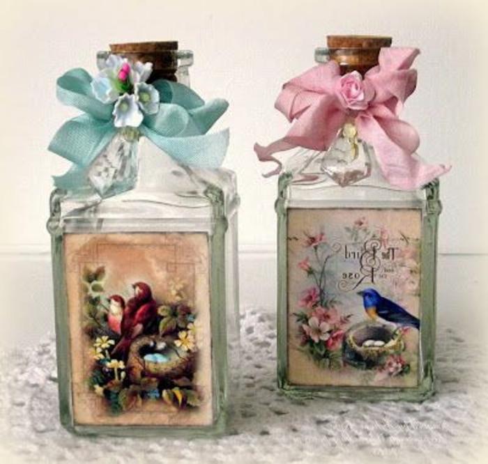 serviettentechnik auf glas - zwei flaschen, eine blaue und eine pinke schleife mit einer einer pinken rosaund zwei servietten mit zwei roten vögel und einem blauen vogel und zwei nestern