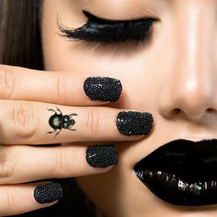 tattoo motive frau deko auf den fingern käfer nageldesign mit steinen schwarze lippen wimpern