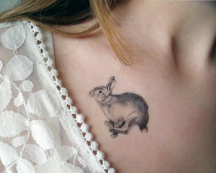 tattoos motive kleine hase springt auf dem schulter einer frau blonde haare spitze bluse dekoration